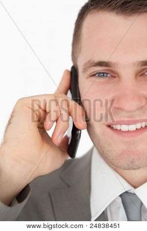 Close up of a smiling businessman making a phone call against a white background