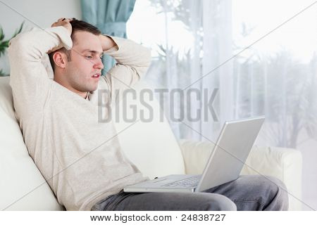 Sad man working with his notebook in his living room