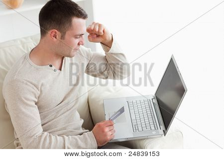 Happy man purchasing online in his living room