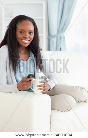 Smiling woman writing text message while having a coffee