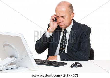 serious businessman sitting at desk in office and talking on mobile phone