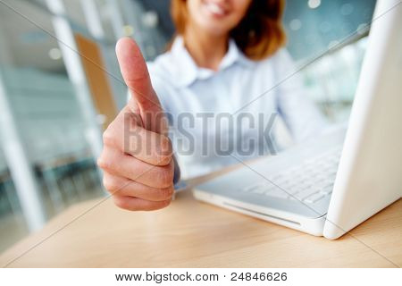 Image of businesswoman showing thumb up at workplace