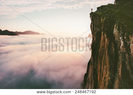 poster of Traveler Standing On Cliff Edge Mountain Top Above Sunset Clouds Travel Adventure Lifestyle Summer J