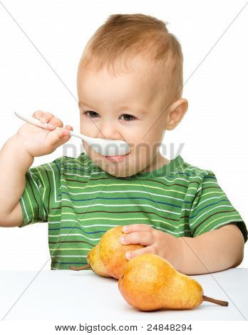 Cute Little Boy With Pears Is Biting Spoon