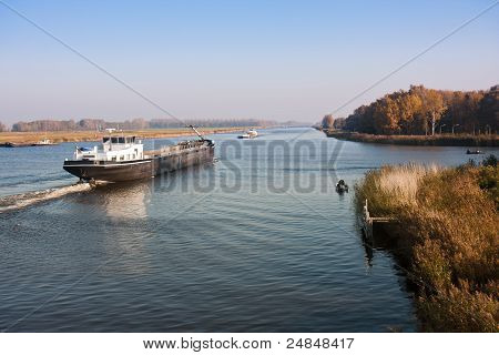 Big Dutch Canal With Fishing Men And A Cargo Vessel