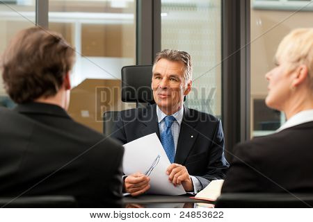 Mature lawyer or notary with clients in his office in a meeting