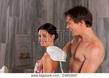 Wellness - couple getting a massage or in the sauna, he is massaging her with gloves