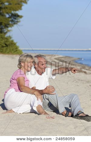 Happy senior man and woman couple together sitting and pointing on a deserted tropical beach