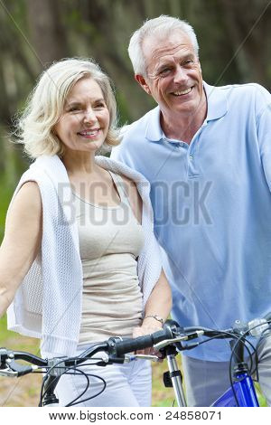 Happy senior man and woman couple sitting together smiling and happy with bicycles at a park