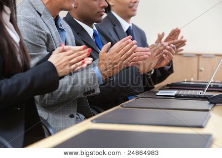 Businesspeople sitting in a row and applauding