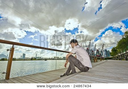 Asian Man Sitting In Park