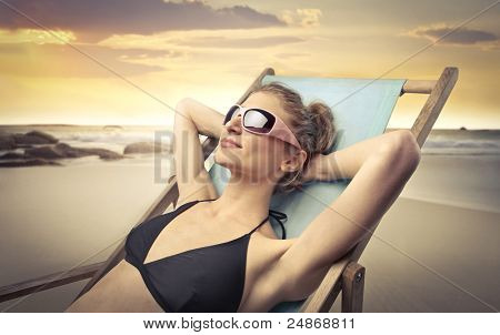 Beautiful woman lying on a deckchair at the seaside