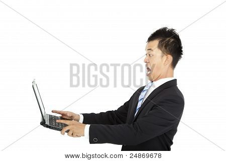 surprised young businessman watching and holding laptop