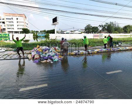 PHATHUMTRANI, Tailândia - 21 de outubro: voluntários resgatar trabalhadores e paredes de saco de areia de construção de exército, durante