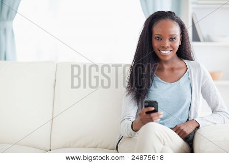 Smiling woman typing a text message on the sofa