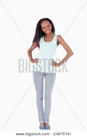 Smiling woman with arms akimbo on white background