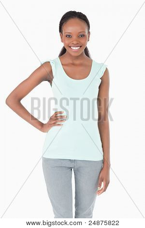 Close up of smiling young woman with one arm akimbo on white background
