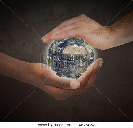 Duas mãos protegendo um globo do planeta brilhante contra um fundo branco