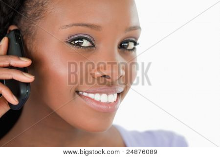 Close up of young woman listening closely to caller on white background