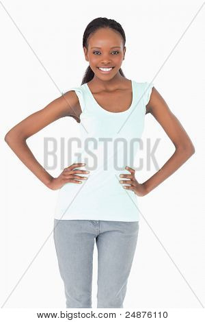 Close up of smiling woman with arms akimbo on white background