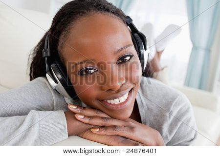 Nahaufnahme, lächelnden Frau mit Musik auf ihrer Couch entspannen