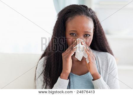 Close up of young woman on sofa blowing her nose
