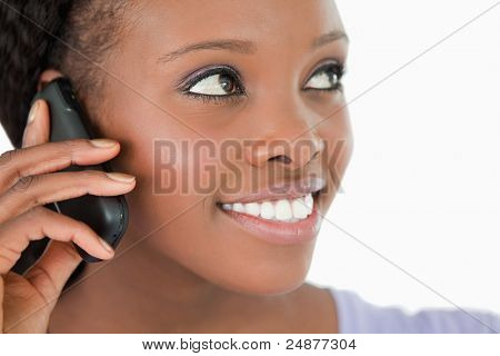 Close up of smiling woman listening to caller on white background