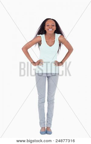 Smiling woman with both arms akimbo on white background