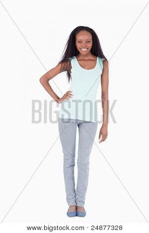 Smiling woman with one arm akimbo on white background