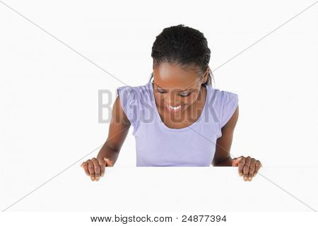 Smiling woman looking down on placeholder on white background
