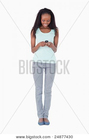 Smiling woman writing text message on white background