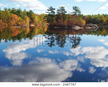 Forest Lake With Autumn Trees And Blue Sky And Clouds Reflected