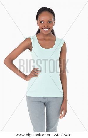 Close up of smiling woman with one arm akimbo on white background