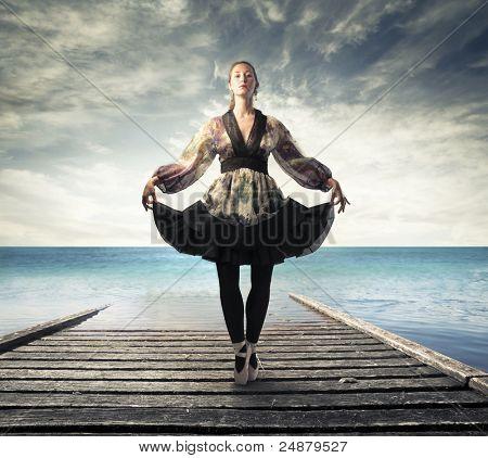 Beautiful elegant ballerina on a pier