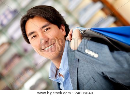 Male shopper at a clothing store holding bags