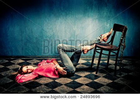 young woman in oriental shirt and shoes lie on tiled floor, legs on chair, studio shot