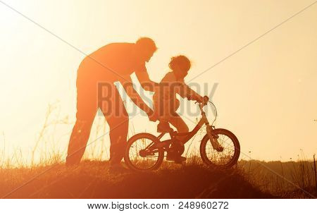 Silhouette of father teaching little