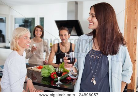 Group of happy female friends enjoying drink in kitchen