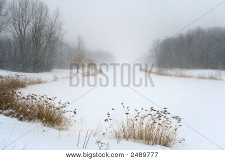 Lake In Misty Haze Of Winter Blizzard