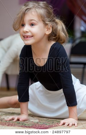 Little girl carries out exercise - cross-section splits. Gap-toothed smile