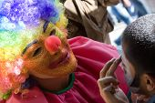 stock photo of face painting  - Here you can see a clown painting the child - JPG