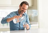 Middle age man drinking a glass of water with a happy face standing and smiling with a confident smi poster