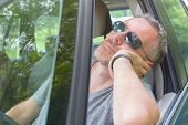 Man driver is resting in the car during a travel break poster