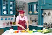Bearded Guy In Apron And Cap Cutting Yellow Paprika For Salad On Cutting Board With White Knife. Han poster