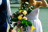 Unidentified Young Wedding Couple. Stylish Bride And Groom Standing With Brides Bouquet Outside On S poster