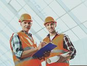 Industrial Engineers Makes Notes And Works With Blueprint In Office. Modern Construction And Enginee poster