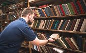 Student Takes A Book From A Shelf In A Public Library. A Man Chooses Books In An Old Public Library. poster