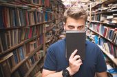 Man In The Library Covers The Face With A Book And Looks At The Camera. Man With A Book In Front Of  poster