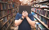 Portrait Of A Man Standing In The Library Covers His Face With An Open Black Book. A Man Hiding Behi poster