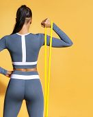 Fitness Girl Performs Exercises For The Muscles Of The Hands With Resistance Band. Photo Of Latin Gi poster